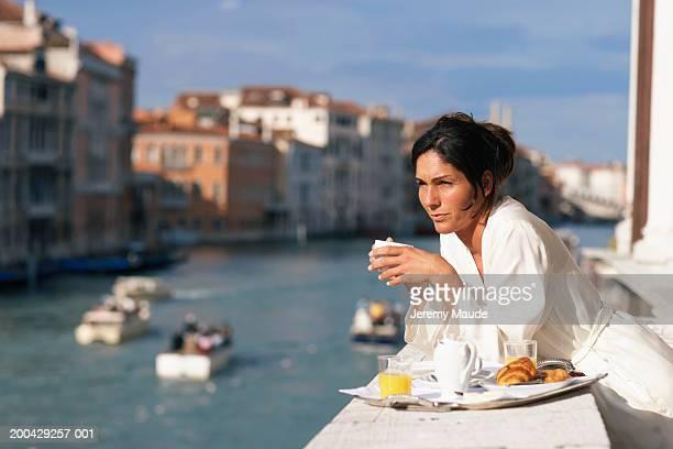 Italy, Venice, woman having breakfast on balcony on canal