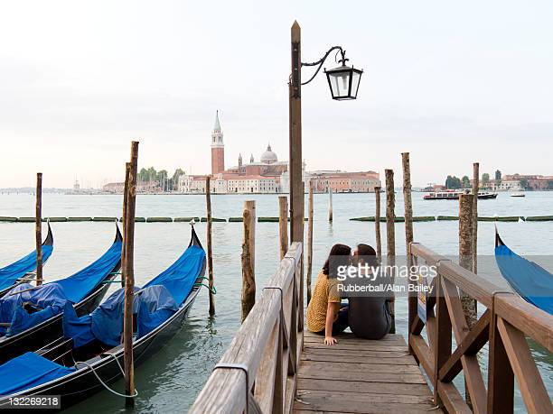 Italy, Venice, Young couple embracing by canal