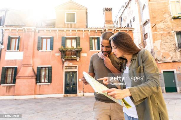 italy, venice, young couple looking at map in the city - 迷う ストックフォトと画像