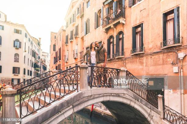 italy, venice, young couple standing on a small bridge exploring the city - venice stock pictures, royalty-free photos & images