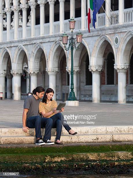 Italy, Venice, Young couple using digital tablet on St. Mark's Square