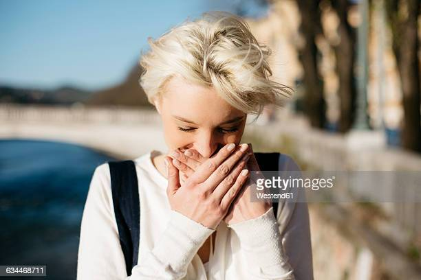 italy, verona, blond woman covering mouth with her hands - hands covering mouth stock pictures, royalty-free photos & images