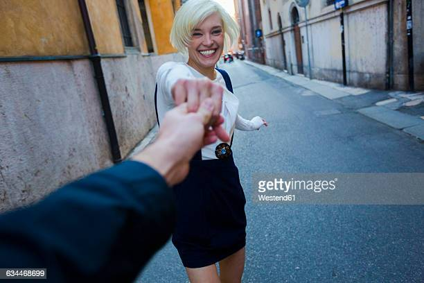 Italy, Verona, portrait of happy blond woman holding hand of her boyfriend