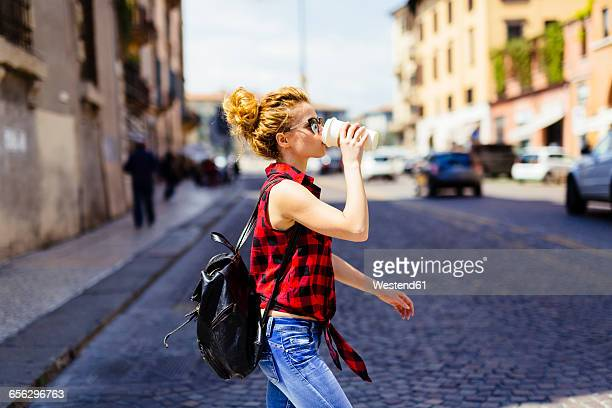 Italy, Verona, woman drinking coffee to go in the city