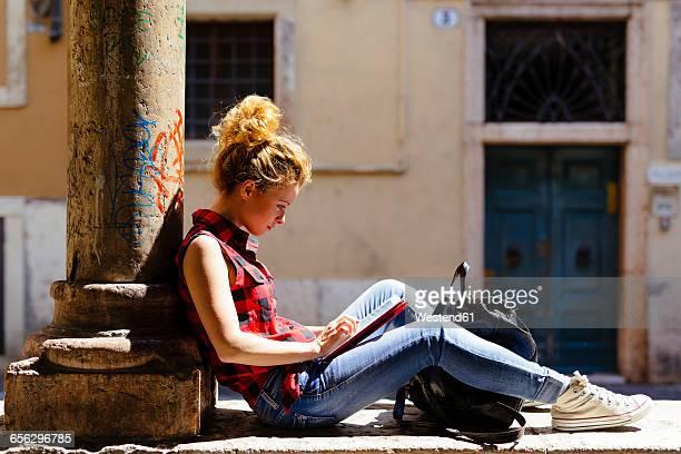 Italy, Verona, woman sitting outdoors using digital tablet