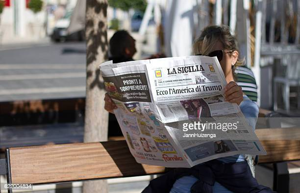 Italy: Woman Reads Newspaper with Headline: Here's Trump's America