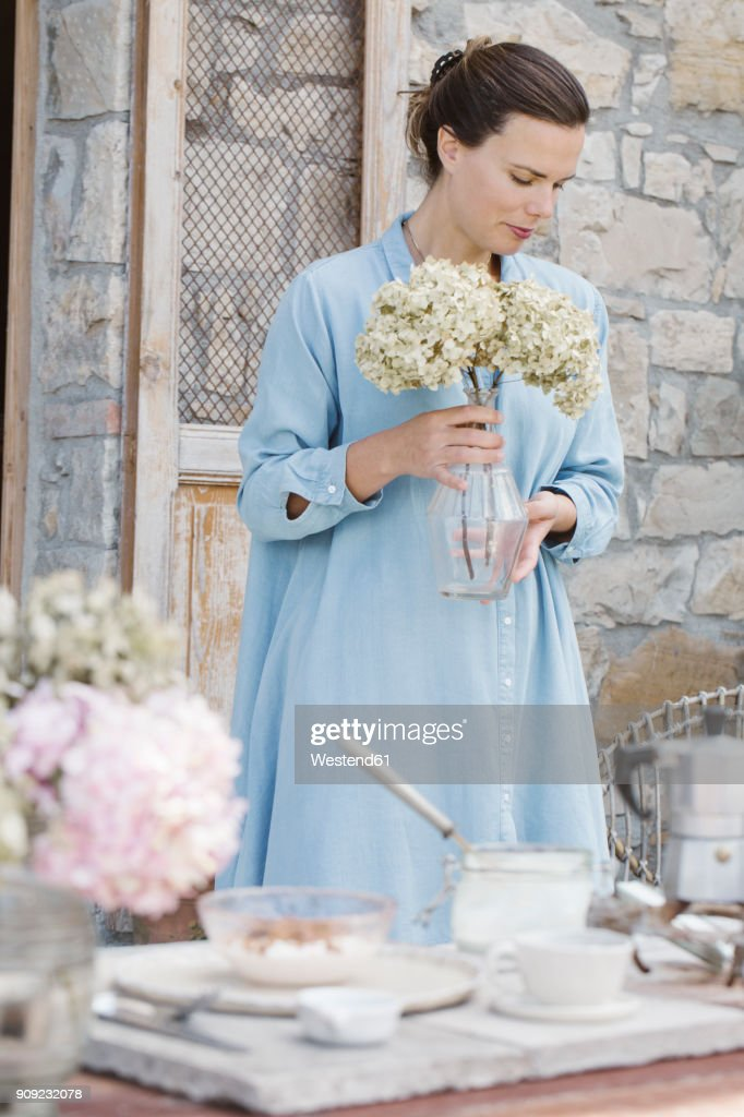 Italy Woman With Flower Heads Of Hortensia In Vase On Terrace Stock