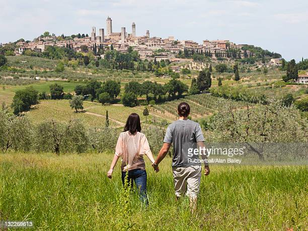 italy, young couple walking in field towards old town - side by side stock photos and pictures