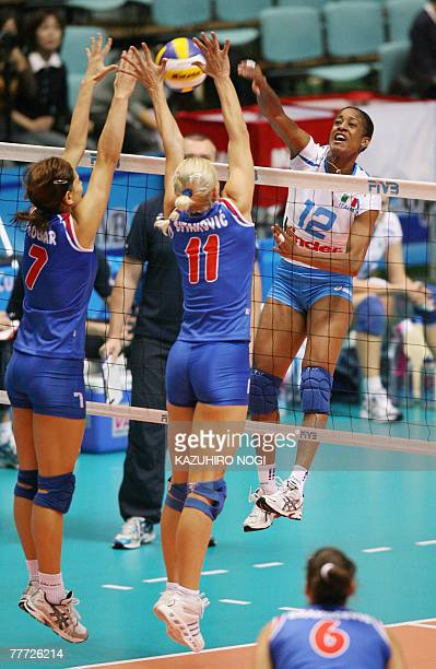 Italy's ace attacker Taismary Aguero spikes the ball against Serbian blockers Brizitka Mohnar and Vesna Citakovic during their second round match at...