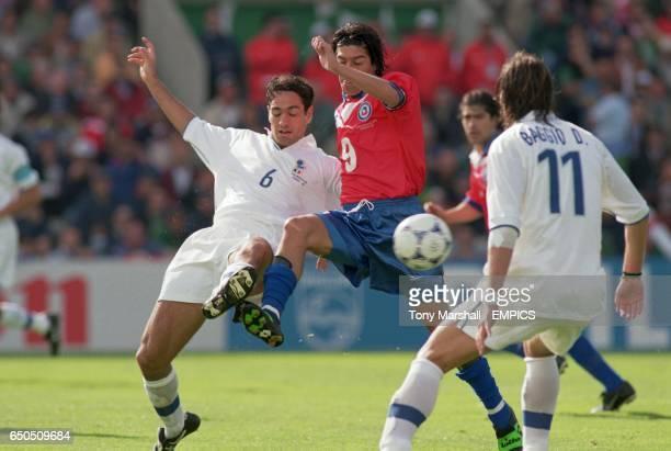 Italy's Alessandro Nesta tackles Chile's Ivan Zamorano as Italy's Dino Baggio looks on