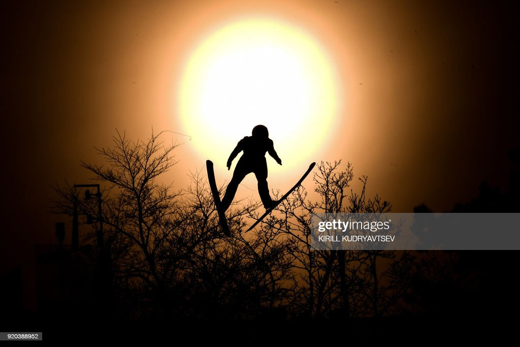 TOPSHOT - Italy's Alessandro Pittin flies through the sun disk during the nordic combined men's individual Gundersen LH/10km official training 3 at the Alpensia ski jump centre during the Pyeongchang 2018 Winter Olympic Games on February 19, 2018 in Pyeongchang. / AFP PHOTO / Kirill KUDRYAVTSEV