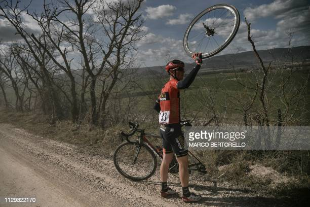 Italy's Andrea Garosio signals a puncture during the oneday classic race Strade Bianche on March 9 2019 in Siena Tuscany