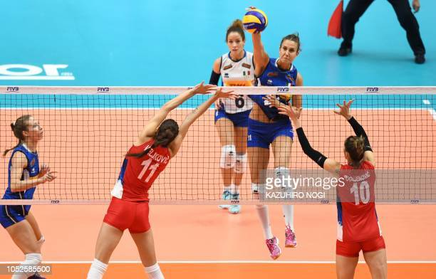 Italy's Anna Danesi spikes the ball over Serbia's Maja Ognjenovic and Stefana Vejikovic during the 2018 FIVB World Championship volleyball women's...