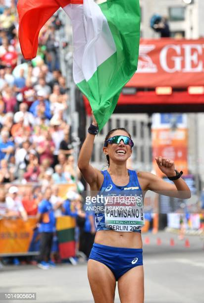 Italy's Antonella Palmisano celebrates as she crosses the finish line to take the third place in the women's 20km walk final race during the European...
