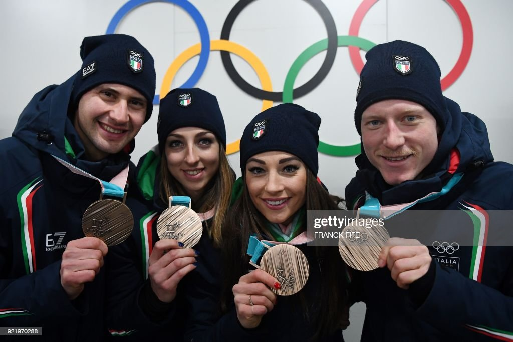 Italy's biathlon bronze medallists Lisa Vittozzi, Dorothea Wierer, Lukas Hofer and Dominik Windisch pose with their medals in front of Olympic rings backstage at the Athletes' Lounge during the medal ceremonies at the Pyeongchang Medals Plaza during the Pyeongchang 2018 Winter Olympic Games in Pyeongchang on February 21, 2018. /