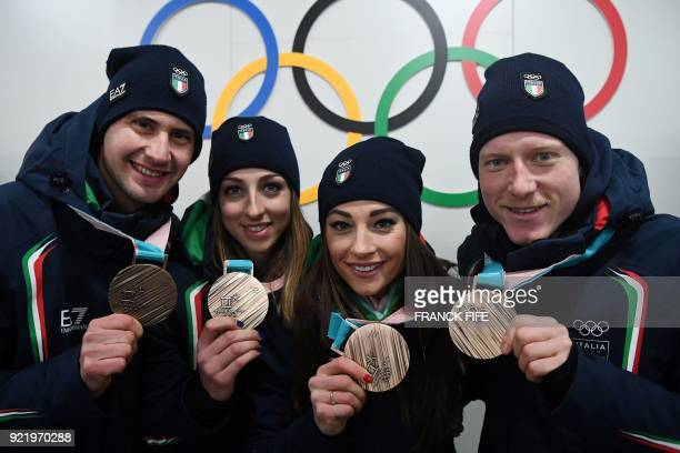 Italy's biathlon bronze medallists Lisa Vittozzi, Dorothea Wierer, Lukas Hofer and Dominik Windisch pose with their medals in front of Olympic rings...