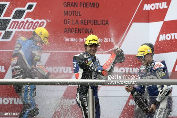 Italy's biker Marco Bezzecchi celebrates on the podiun after winning the Moto3 race next to secondplaced Spain's Aron Canet and thirdplaced Italy's...