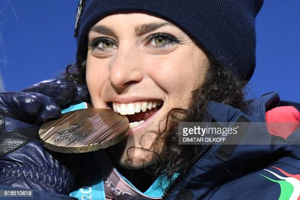 TOPSHOT Italy's bronze medallist Federica Brignone bites her medal on the podium during the medal ceremony for the women's alpine skiing giant slalom...