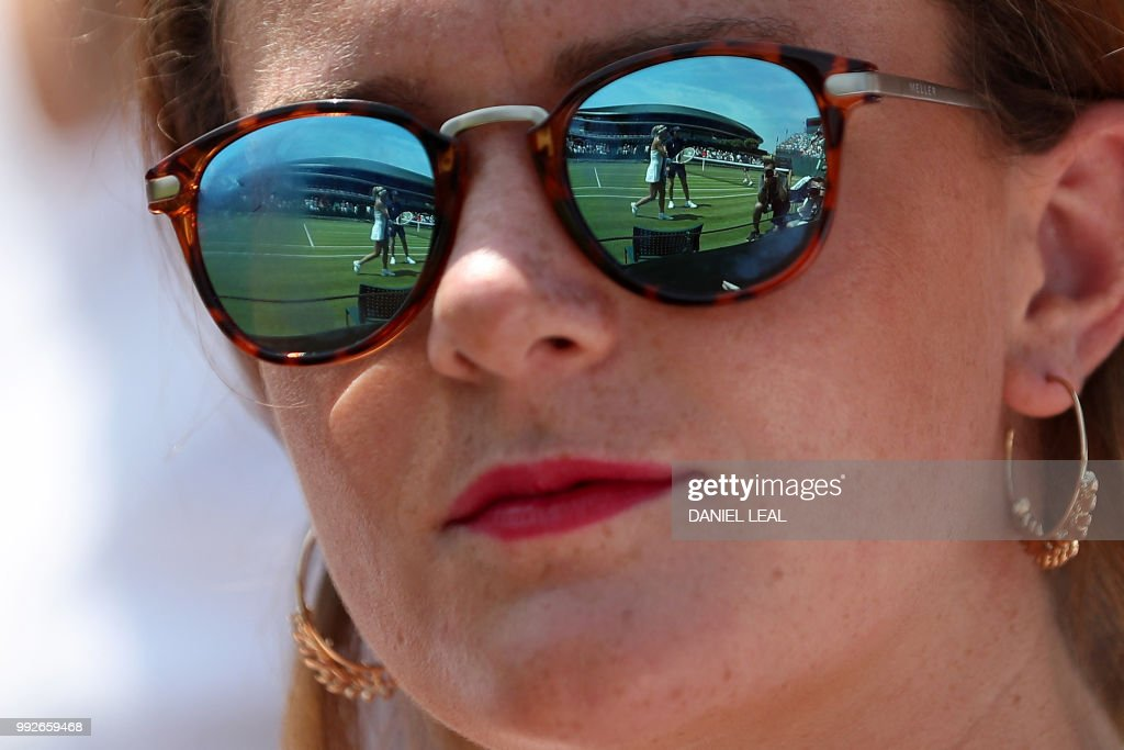 TOPSHOT - Italy's Camila Giorgi is reflected in a spectator's sunglasses as she plays against Czech Republic's Katerina Siniakova during their women's singles third round match on the fifth day of the 2018 Wimbledon Championships at The All England Lawn Tennis Club in Wimbledon, southwest London, on July 6, 2018. (Photo by Daniel LEAL-OLIVAS / AFP) / RESTRICTED