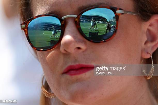 TOPSHOT Italy's Camila Giorgi is reflected in a spectator's sunglasses as she plays against Czech Republic's Katerina Siniakova during their women's...