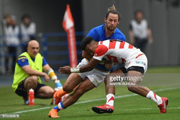 Italy's centre Michele Campagnaro is tackled by Japan's fullback Kotaro Matsushima during the rugby union Test match between Japan and Italy at the...