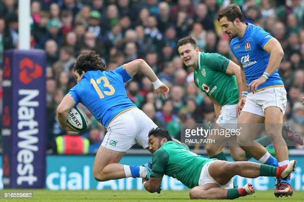 Italy's centre Tommaso Boni is tackled by Ireland's centre Bundee Aki during the Six Nations international rugby union match between Ireland and...