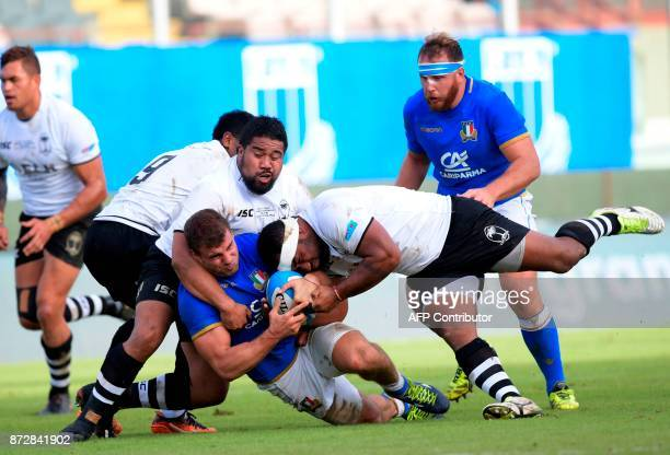 Italy's centre Tommaso Castello is tackled by Fiji's prop Campese Maafu and Fiji's hooker Tuapati Talemaitoga during a rugby union test match between...