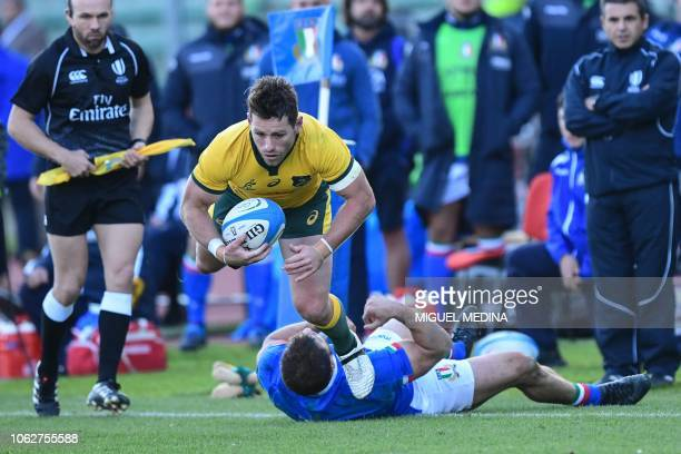 Italy's centre Tommaso Castello tackles Australia's centre Bernard Foley during the international rugby union test match Italy vs Australia on...