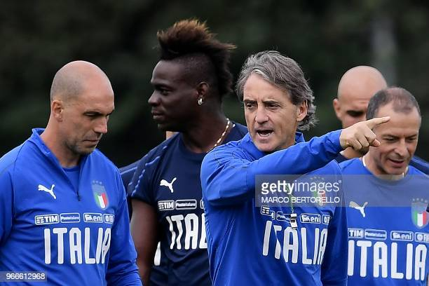 Italy's coach Roberto Mancini gestures past Italy's forward Mario Balotelli during a training session on June 3 2018 on the eve of their...