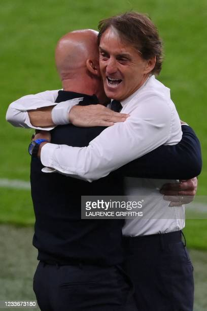 Italy's coach Roberto Mancini reacts after Italy's midfielder Federico Chiesa scored the team's first goal during extra time in the UEFA EURO 2020...