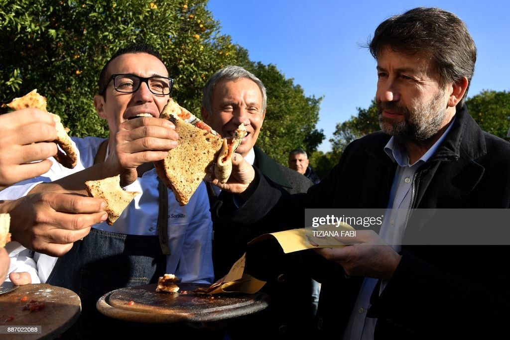 Italy's Culture Minister Dario Franceschini (R) shares a pizza with some 'Pizzaioli' (pizza makers) at the Capodimonte museum hosting the first stone oven where was cooked a Pizza Margherita, on December 6, 2017 in Naples. Naples' art of pizza twirling is a candidate to join UNESCO's list of 'intangible heritage' and the city is waiting for the decision of the UN cultural body's World Heritage Committee which is reunited in South Korean island of Jeju this week. /