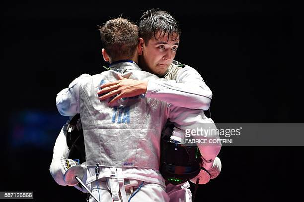 Italy's Daniele Garozzo embraces US Alexander Massialas after winning their mens individual foil gold medal bout as part of the fencing event of the...
