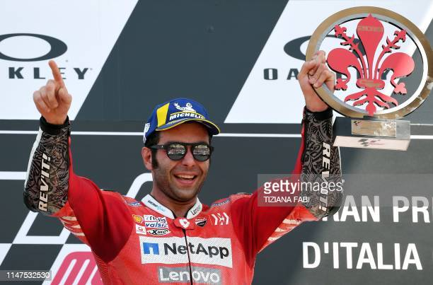 Italy's Danilo Petrucci holds his trophy as he celebrates on the podium after winning the Italian Moto GP Grand Prix at the Mugello race track on...