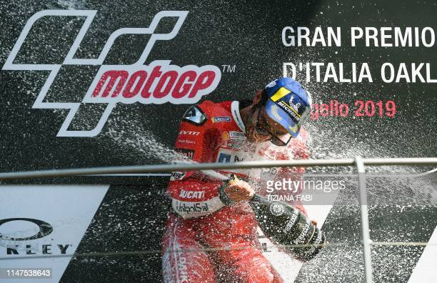 TOPSHOT Italy's Danilo Petrucci sprays champagne as he celebrates on the podium after winning the Italian Moto GP Grand Prix at the Mugello race...