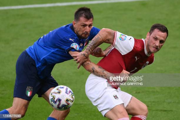 Italy's defender Francesco Acerbi and Austria's forward Marko Arnautovic vie for the ball during the UEFA EURO 2020 round of 16 football match...