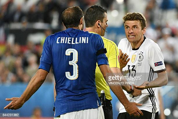 TOPSHOT Italy's defender Giorgio Chiellini and Germany's midfielder Thomas Mueller react as Hungarian referee Viktor Kassai stands separating them...