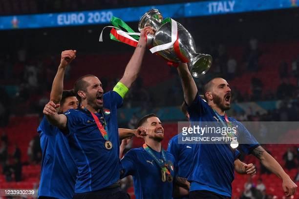 Italy's defender Giorgio Chiellini and Italy's defender Leonardo Bonucci pose with the European Championship trophy after Italy won the UEFA EURO...