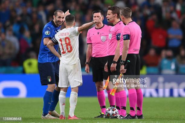 Italy's defender Giorgio Chiellini and Spain's defender Jordi Alba argue at which and of the filed the penalty shootout should be at during the UEFA...