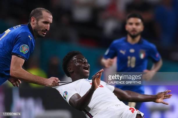 Italy's defender Giorgio Chiellini fouls England's midfielder Bukayo Saka during the UEFA EURO 2020 final football match between Italy and England at...