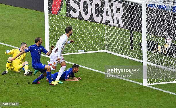 TOPSHOT Italy's defender Giorgio Chiellini looks at the ball after scoring a goal beside Spain's goalkeeper David De Gea and Spain's defender Gerard...
