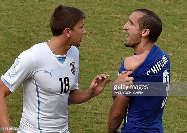 Italy's defender Giorgio Chiellini shows an apparent bitemark by Uruguay forward Luis Suarez to Uruguay's midfielder Gaston Ramirez during a Group D...