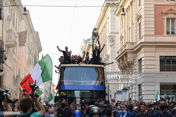 Italy's defender Leonardo Bonucci holds the UEFA EURO 2020 trophy as Italy's national football team players parade on a double decker bus in Rome on...