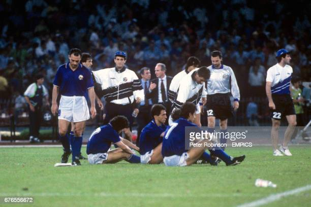 Italy's dejected players sitting the turf following their elimination via a penalty shootout with Argentina