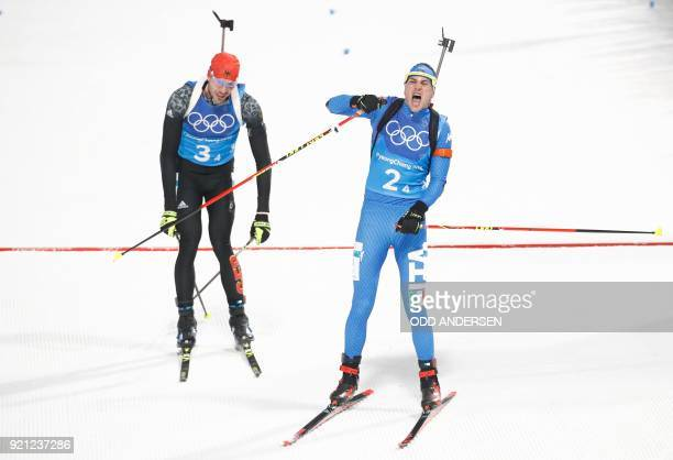 TOPSHOT Italy's Dominik Windisch crosses the finish line to win bronze followed by Germany's Simon Schempp in the mixed relay biathlon event during...