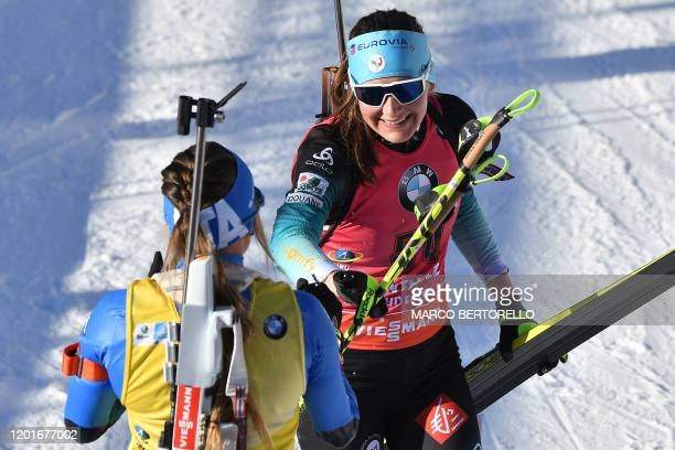 Italy's Dorothea Wierer and France's Justine Braisaz tap hands after crossing the finish line of the IBU Biathlon World Cup Women's 15 km Individual...