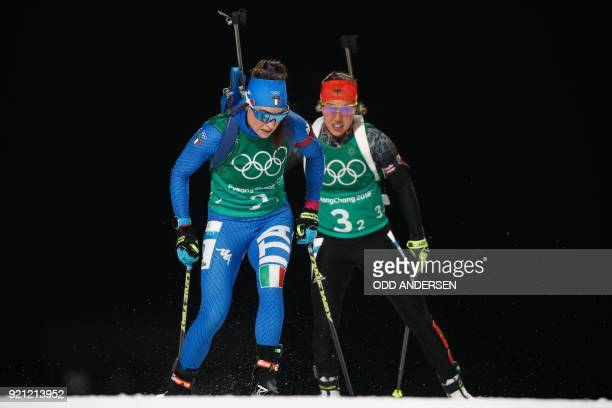 Italy's Dorothea Wierer and Germany's Laura Dahlmeier compete in the mixed relay biathlon event during the Pyeongchang 2018 Winter Olympic Games on...