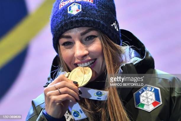 Italy's Dorothea Wierer bites her gold medal on the podium after winning the IBU Biathlon World Cup 10 km Women's pursuit in RasenAntholz Italian...