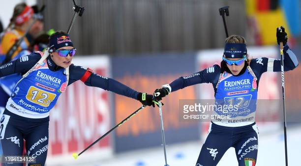 Italy's Dorothea Wierer hands over to Italy's last starter Federica Sanfilippo during the women's 4x6km relay event at the Biathlon World Cup in...