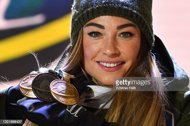 Italy's Dorothea Wierer poses with two gold medals and one silver medal she won so far on the podium after winning the IBU Biathlon World Cup Women's...