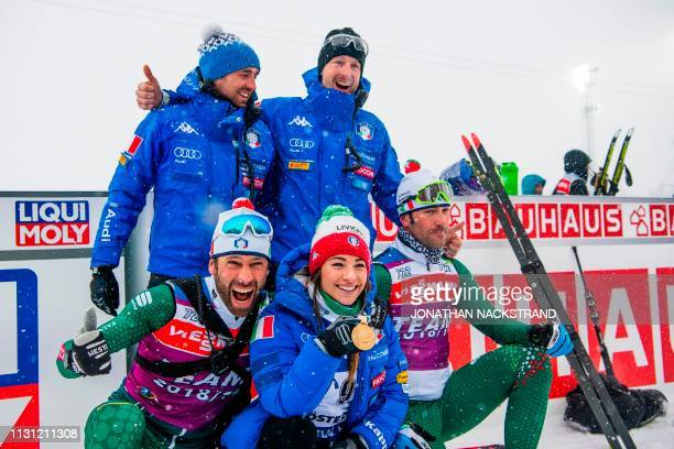 Italy's Dorothea Wierer presents her gold medal as she poses with team mates after winning the women's 12,5 km mass start event at the IBU World...